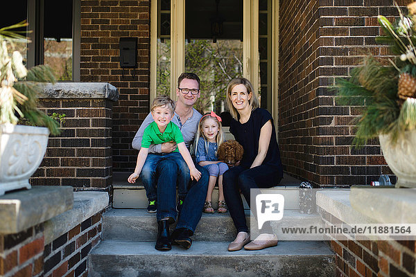 Portrait of parents sitting on porch steps with daughter and son