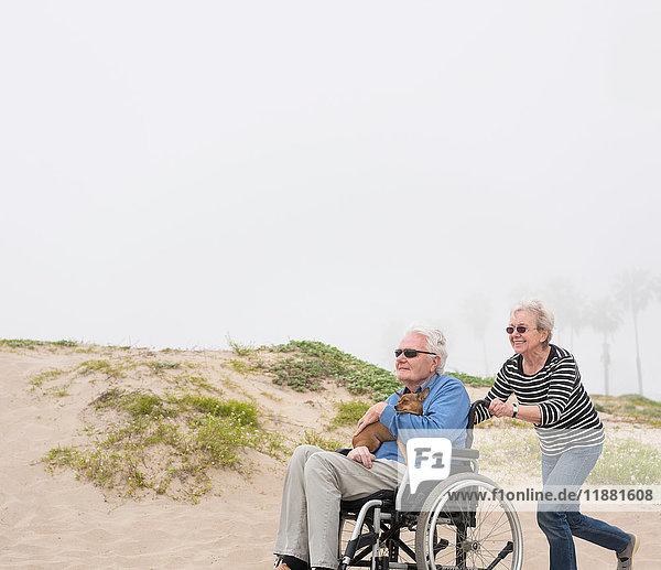 Senior woman pushing husband in wheelchair on dunes  Playa del Ray  California  USA