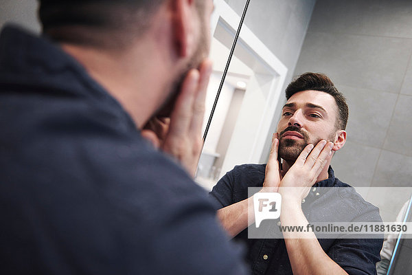 Mirror image of bearded man with hands on face