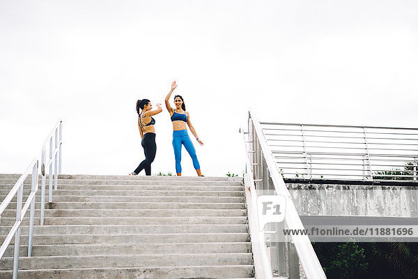 Zwei junge Frauen oben auf der Treppe  die das Training feiern  South Point Park  Miami Beach  Florida  USA