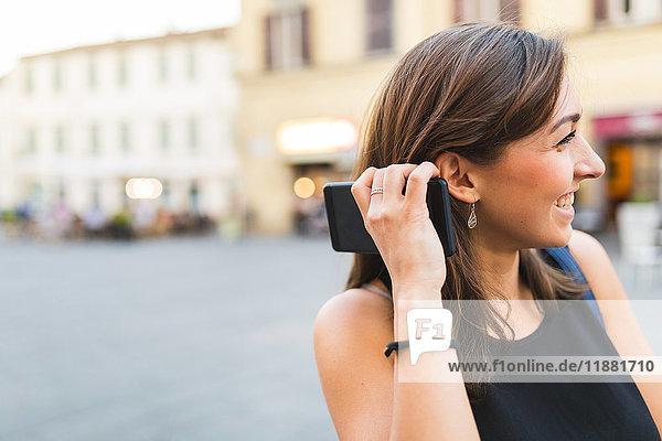 Junge Frau in der Stadt hält Smartphone in der Hand und schaut lächelnd weg