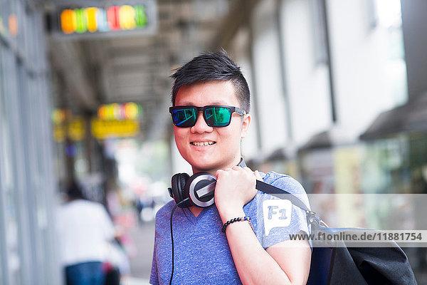 Porträt eines Mannes mit Kopfhörer und Sonnenbrille  der lächelnd in die Kamera schaut