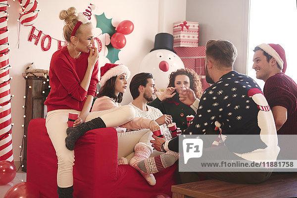 Junge Frauen und Männer essen auf der Weihnachtsfeier Popcorn auf dem Sofa