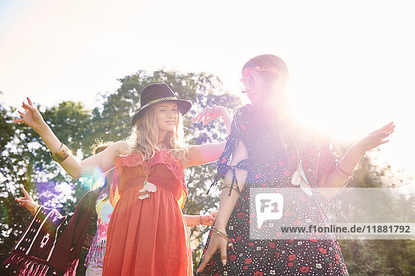 Two young boho women dancing in sunlight at festival