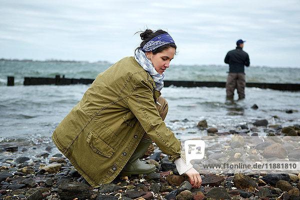 Junge Frau kauert am Strand  während ihr Freund im Meer fischt