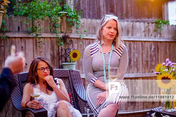 Zwei Frauen bei Gartenparty  sitzend  im Gespräch