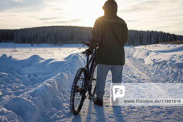 Rear view of male mountain biker watching sunset over snow covered landscape