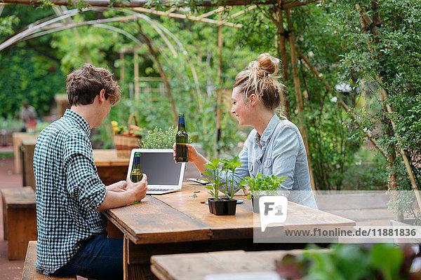 Paar mit Bier im Garten mit Laptop