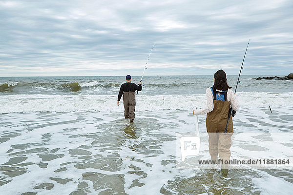 Young sea fishing couple in waders  wading in sea