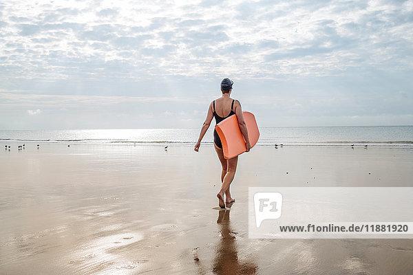 Woman carrying surfboard on beach  Folkestone  UK