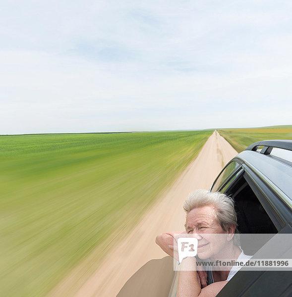 Senior woman leaning on car window enjoying wind in face