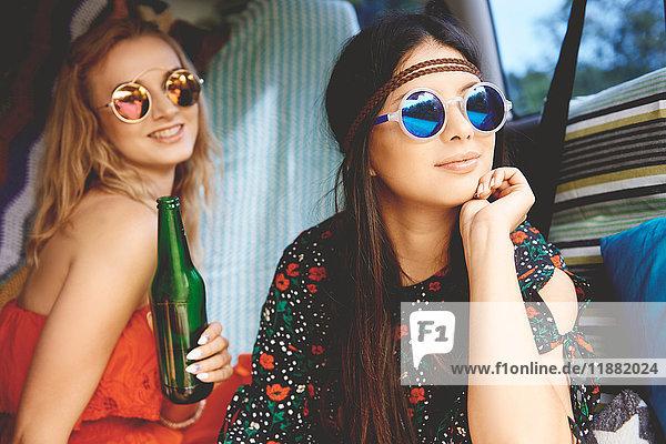 Zwei junge Boho-Frauen mit Sonnenbrille im Wohnwagen