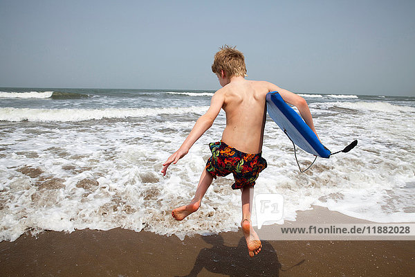 Rear view of boy with bodyboard jumping in sea  Goa  India  Asia