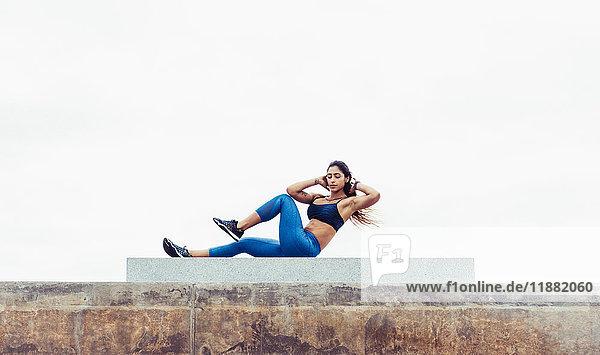 Junge Frau übt im Freien  macht Sit-ups  South Point Park  Miami Beach  Florida  USA