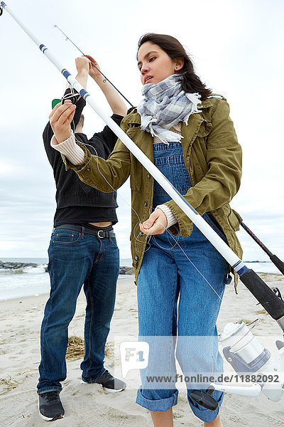 Young couple preparing sea fishing rods on beach