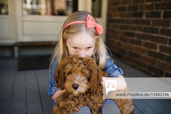 Portrait of girl kissing red haired puppy on front porch