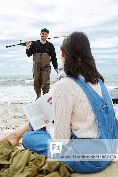 Junge Frau betrachtet Meeresfischer-Freund am Strand