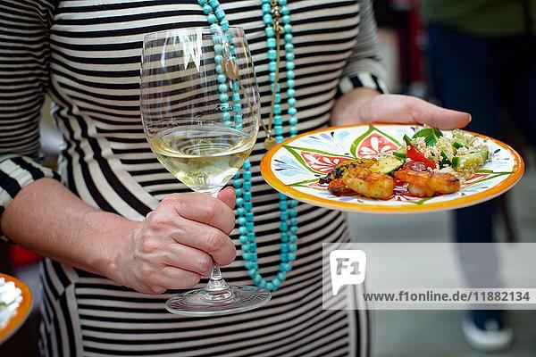 Frau hält ein Glas Wein und einen Teller mit Essen  Mittelteil