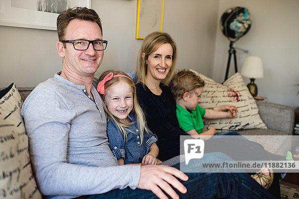 Porträt der auf dem Sofa sitzenden Eltern mit Tochter und Sohn