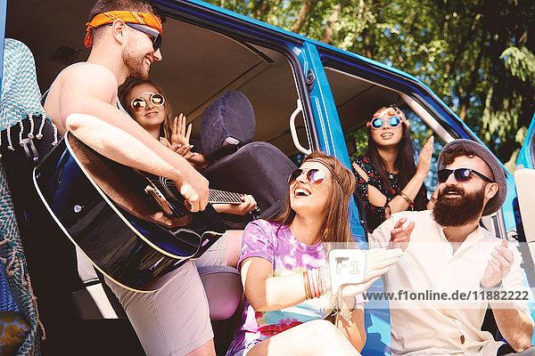 Fünf junge erwachsene Freunde spielen Akustikgitarre und klatschen im Wohnwagen