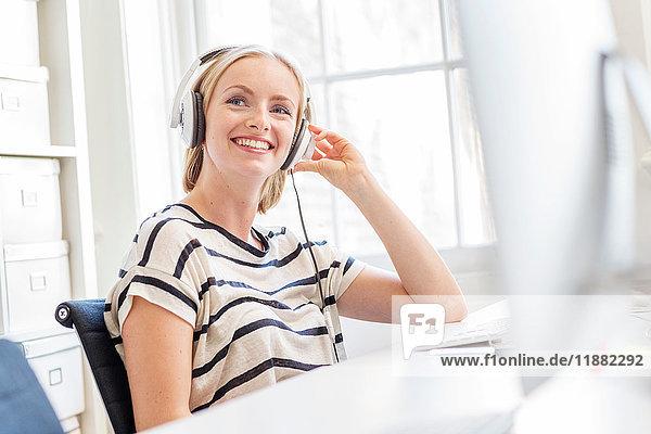 Designerin hört Kopfhörer am kreativen Studiotisch