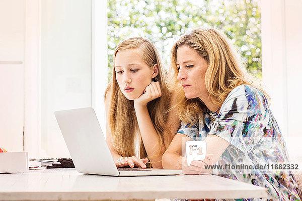 Mutter und Tochter benutzen Laptop