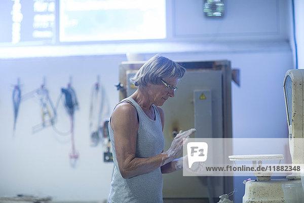 Ältere Frau in Töpferwerkstatt  wiegt Ton für Töpferprojekt