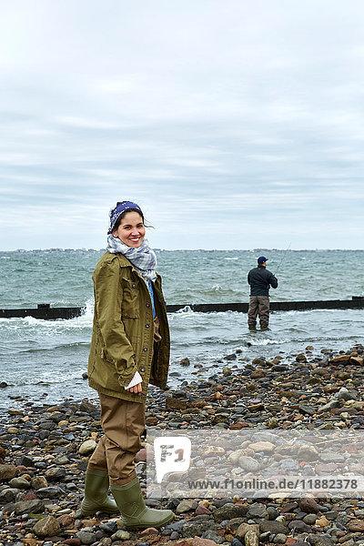 Porträt einer jungen Frau am Strand  während ihr Freund im Meer fischt