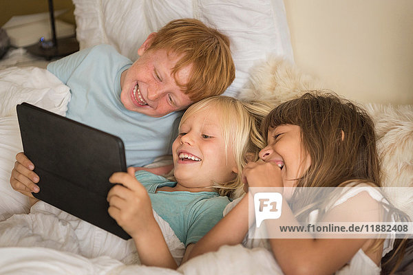 Children lying in bed looking at digital tablet