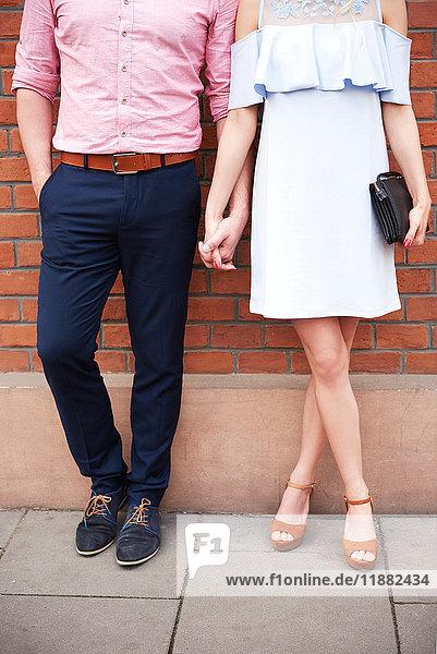 Schrägansicht eines Paares  das sich vor einer Ziegelmauer an den Händen hält