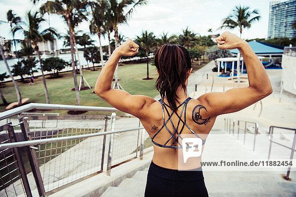 Junge Frau im Freien  oben auf den Stufen stehend  Muskeln anspannen  Rückansicht  South Point Park  Miami Beach  Florida  USA