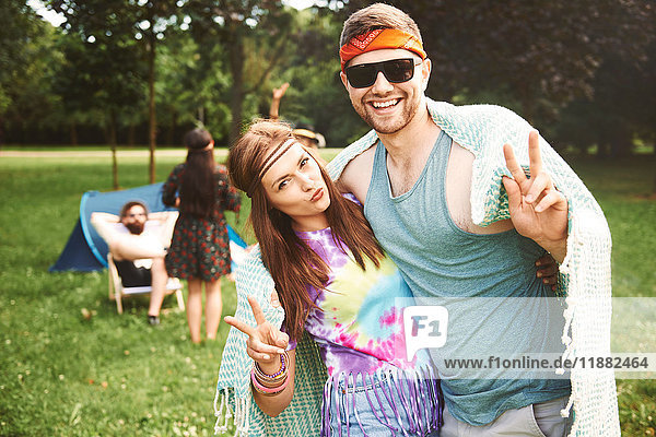 Porträt eines jungen Boho-Paares  das auf dem Festival Friedenszeichen setzt
