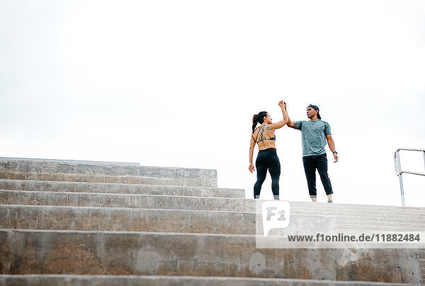 Junger Mann und Frau oben auf der Treppe  feiern das Training  South Point Park  Miami Beach  Florida  USA