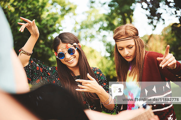 Two young boho women dancing together at festival