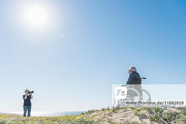 Senior woman photographing husband in wheelchair on dunes  Playa del Ray  California  USA