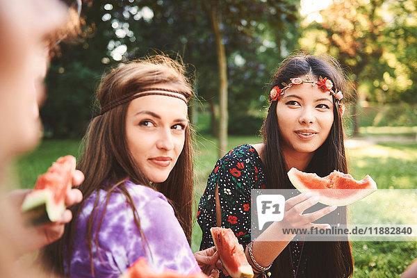 Junge Boho-Frauen essen Melonenscheibe beim Festival