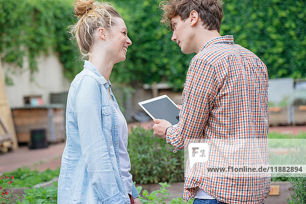Ehepaar im Garten mit digitalem Tablett