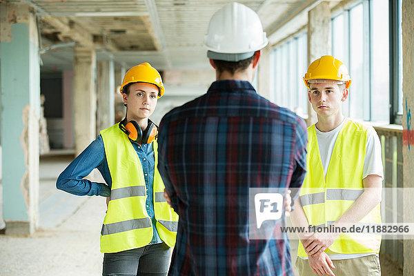 Drei Personen stehen auf der Baustelle  tragen Schutzhelme und diskutieren