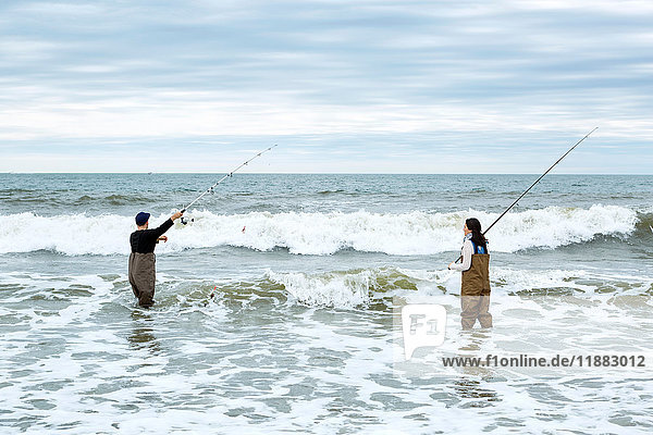 Young couple in waders  casting off sea fishing rods in sea