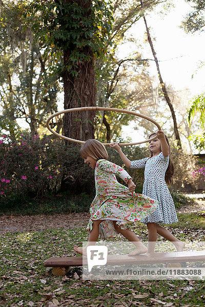 Girl holding plastic hoop above her sister's head