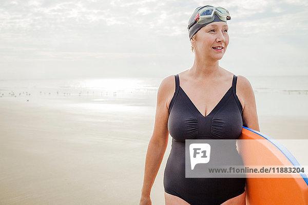 Frau trägt Surfbrett am Strand  Folkestone  UK