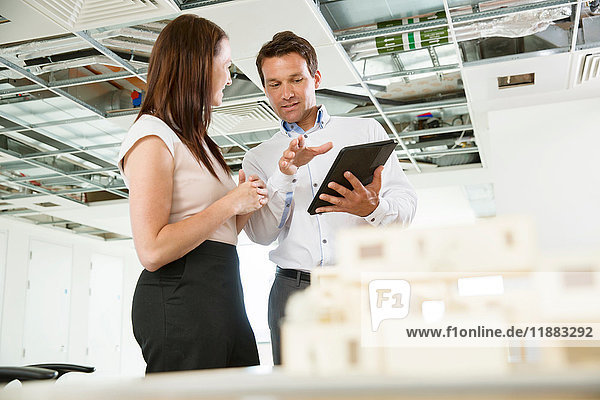 Businessman and woman having discussion  looking at digital table  architectural model on tablet  low angle view