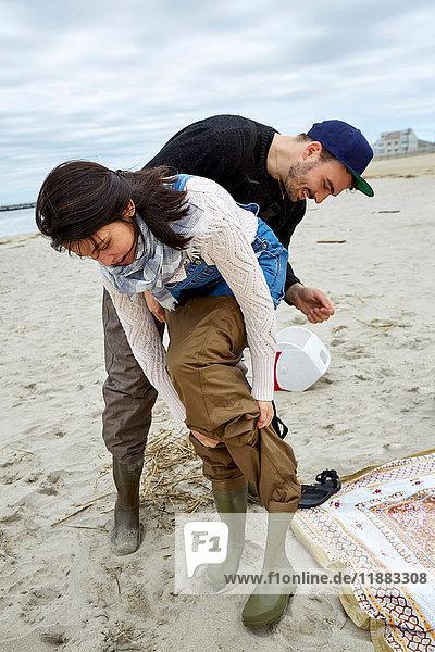 Junges Hochseefischerpaar zieht am Strand Wathosen an