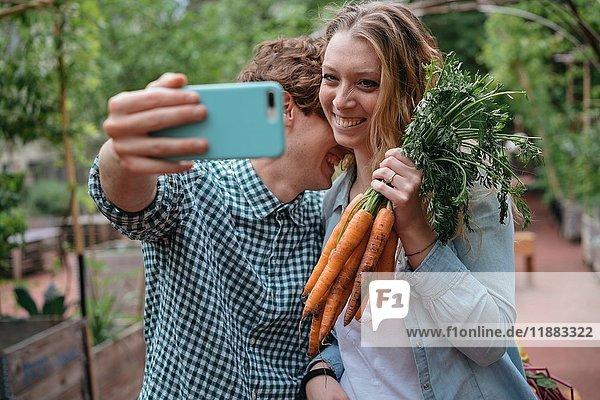 Pärchen im Garten mit Karotten  die Selbsthilfe nehmen