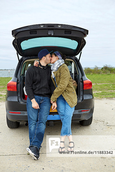 Young couple sitting in open car boot  kissing