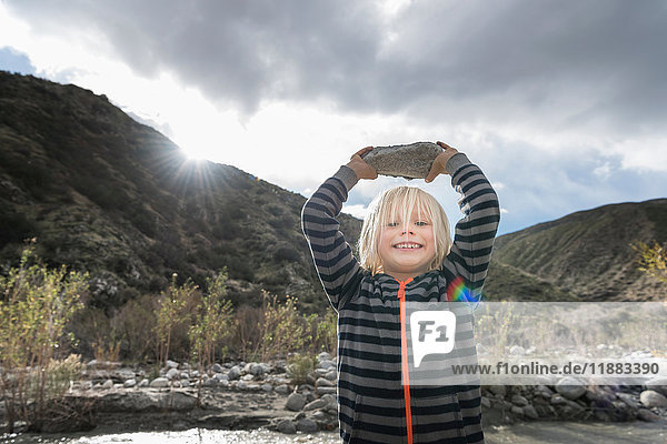 Portrait of cute boy holding up rock from riverbed