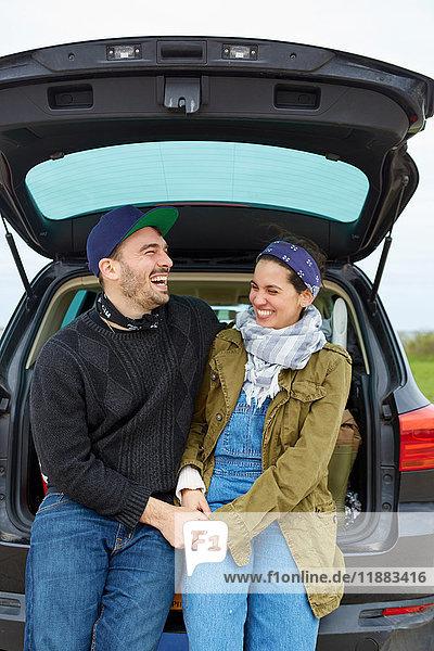 Junges Paar sitzt im offenen Kofferraum eines Autos  hält Händchen und lacht