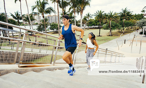 Man and woman exercising outdoors  running up steps  elevated view  South Point Park  Miami Beach  Florida  USA