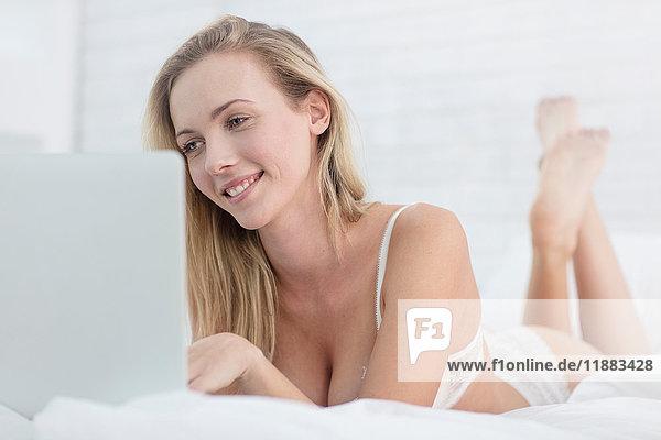 Junge Frau  die auf dem Bett liegt  Unterwäsche trägt und einen Laptop benutzt