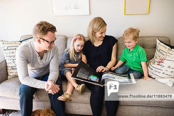 Eltern auf dem Sofa  die ihrem Sohn und ihrer Tochter ein Märchenbuch vorlesen